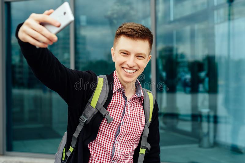 Casual happy young man in plaid shirt making selfie outdoors. He city and making selfie outdoors. Student with cell phone walking on street. Technology and stock images
