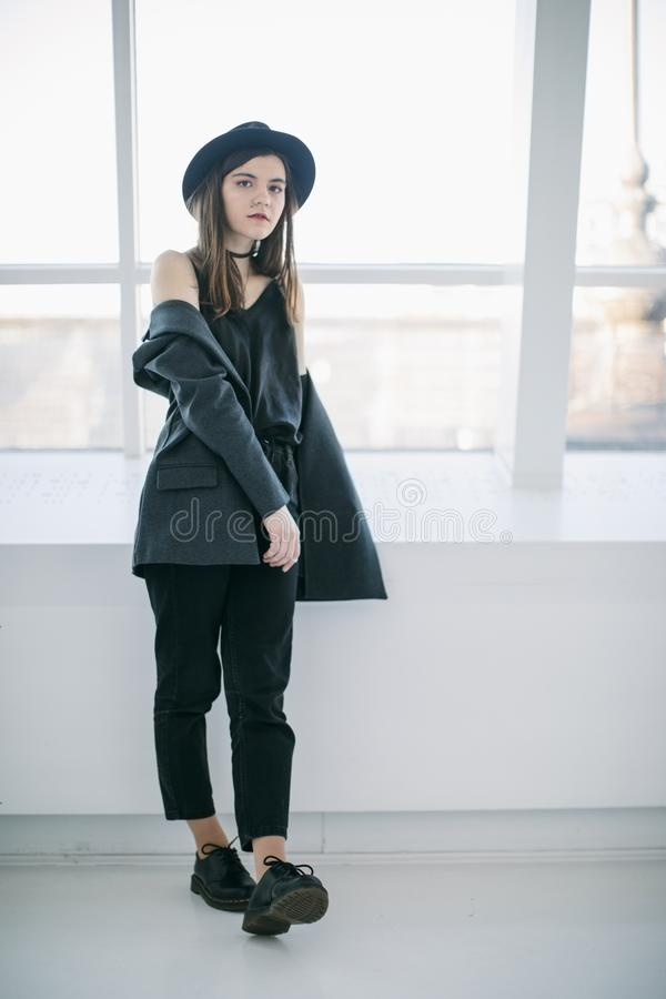 Casual hipster style young woman portrait. girl standing near the window in full growth. Soft daylight. Relaxed mood royalty free stock photos