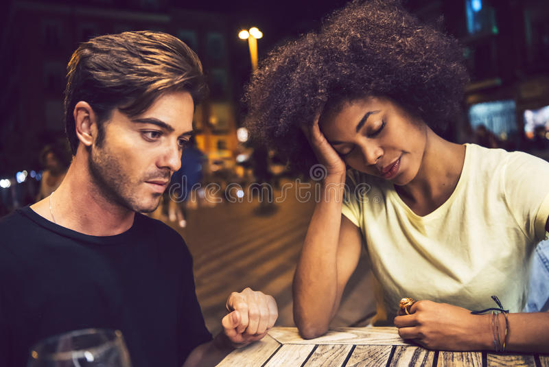 Casual interracial couple having an argument in a terrace.  stock photo