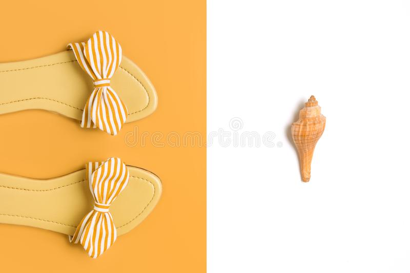 Casual ladies beach sandals and sea shell concept image. stock photography
