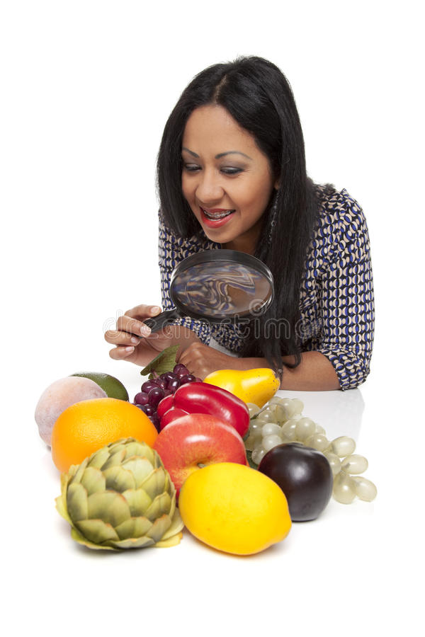 Casual Latina - produce selection magnifying glass. Isolated studio shot of a Latina woman using a magnifying glass to exam fruits and vegetables, deciding what stock photography