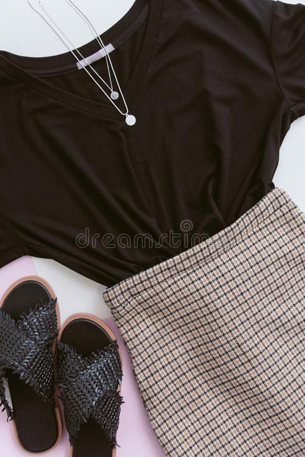 Casual look on a pastel pink background. black shirt, plaid skirt and silver pendants. black straw sandals. summer concept of royalty free stock photos