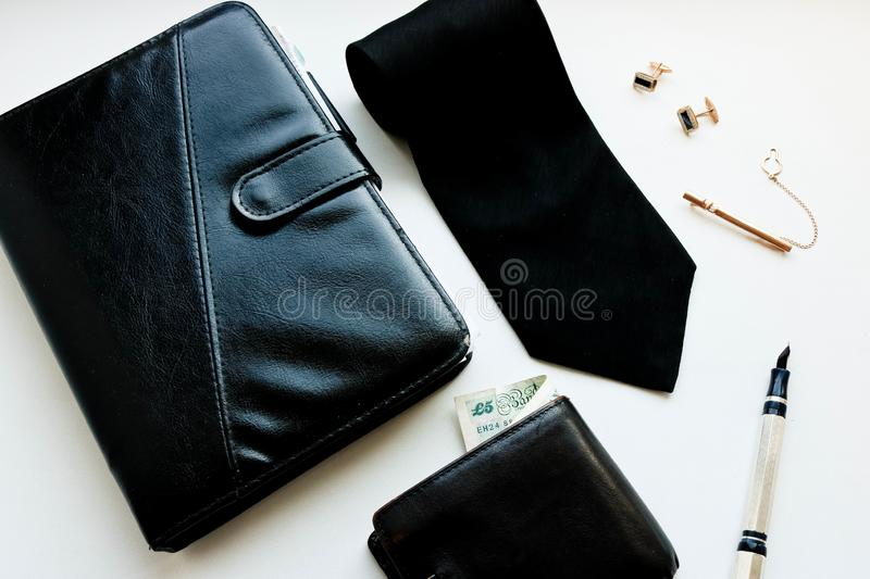Casual males accessories flat lay with black notepad tie cufflinks tie clip wallet and pen. White background stock photos