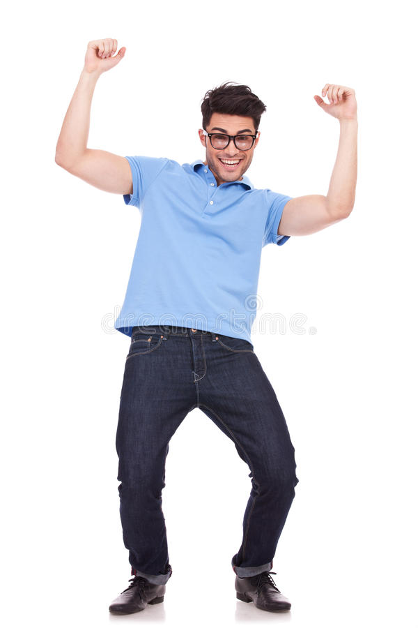 Casual man celebrating. Happy young casual man celebrating, cheering with both his arms in the air, isolated over a white background royalty free stock images