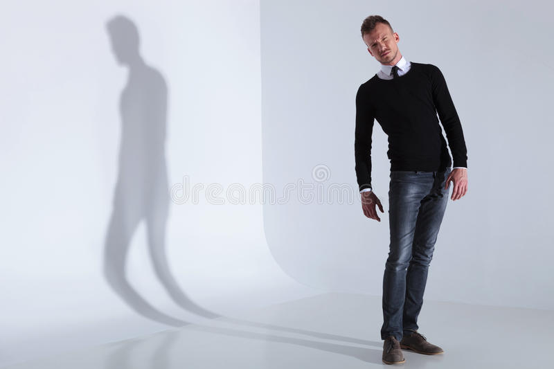 Casual man in a confuse pose. Full length picture of a casual young man looking at the camera with a confuse expression. on light gray studio background with royalty free stock images