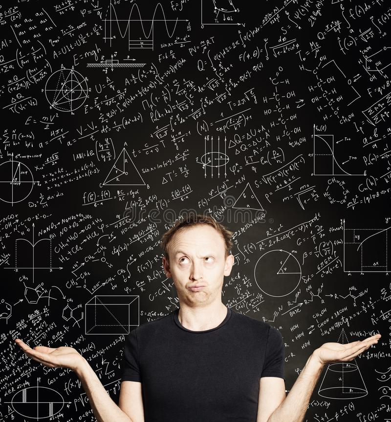 Casual man with empty open hands on blackboard science background. Education, student exam and brainstorm concept royalty free stock image