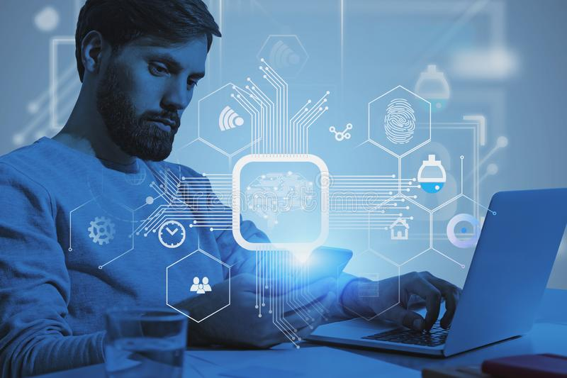 Casual man with gadgets, machine learning. Serious young programmer in casual clothes using laptop and smartphone with double exposure of machine learning royalty free stock images