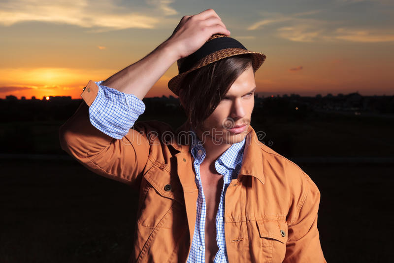 Casual man with hand on hat looks away royalty free stock photo