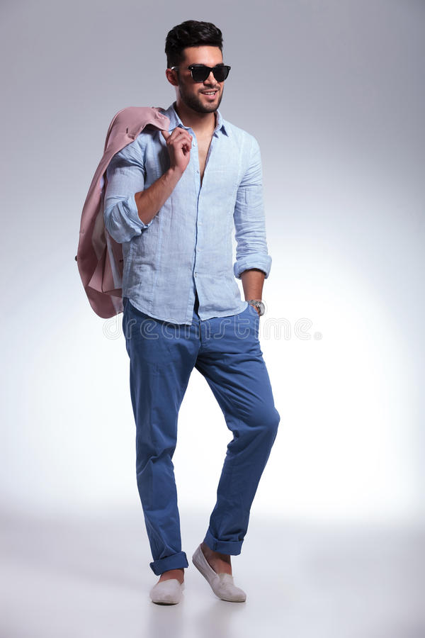 Casual man with hand in pocket and jacket on shoulder. Full length portrait of a young casual man smiling with his jacket over his shoulder and a hand in his royalty free stock images
