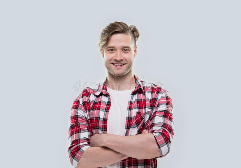 Casual Man Happy Smile Young Handsome Guy Folded Hands Wear Checked Shirt. Over Grey Background stock photo