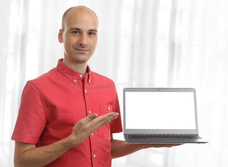 Casual man holding laptop computer. Pointing to blank screen royalty free stock photo