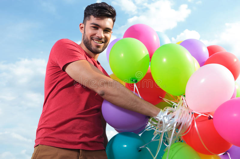 Casual man holds a lot of baloons. Casual man holds a lot of balloons stock photography