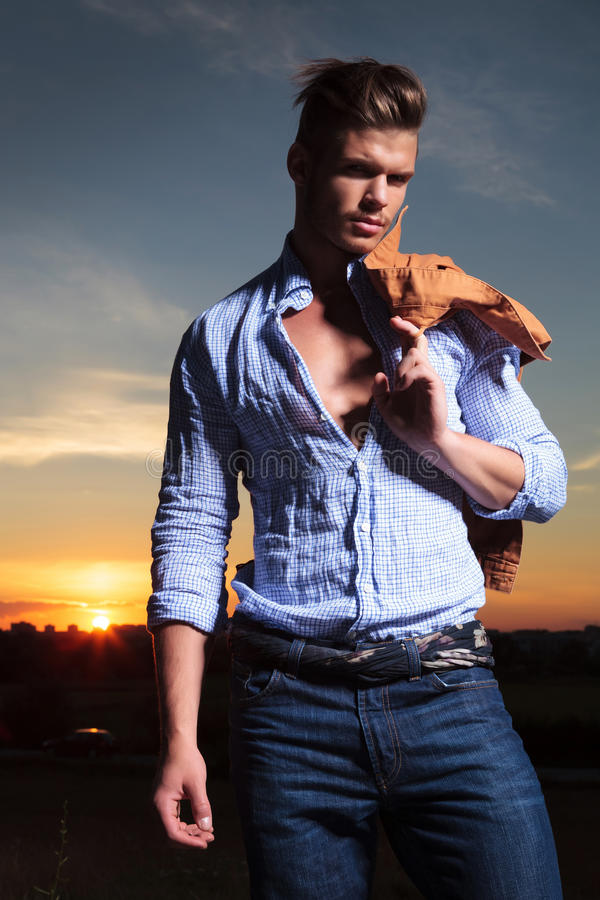 Casual man with jacket on shoulder, at sunset. Casual young man standing outdoor with his jacket over his shoulder with the sunset behind him stock image
