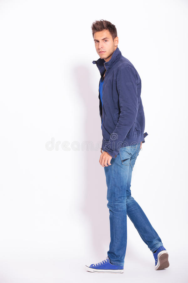 Casual man in jeans and jacket turning to the camera stock images