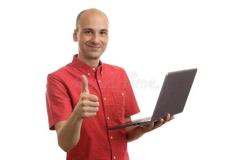 Casual man with laptop showing thumbs up. Casual bald man with laptop showing thumbs up. Isolated over white royalty free stock photography