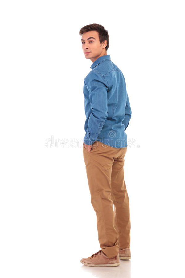 Casual man looking back over his shoulder. Full body picture of a casual man looking back over his shoulder on white background, back view stock images