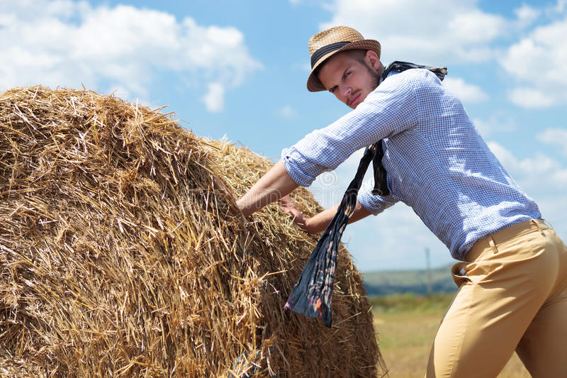 Casual man outdoor pushing a big round haystack. Young casual man posing outdoor, pushing a big round haystack and looking into the camera stock images