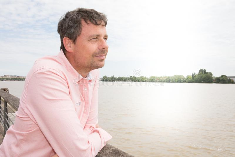 Casual man outdoors looking up Garonne river and smiling in the Bordeaux city in France stock photography