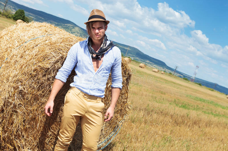 Casual man posing on the field, next to haystack. Young casual man posing outdoor next to a big round haystack and looking into the camera royalty free stock images