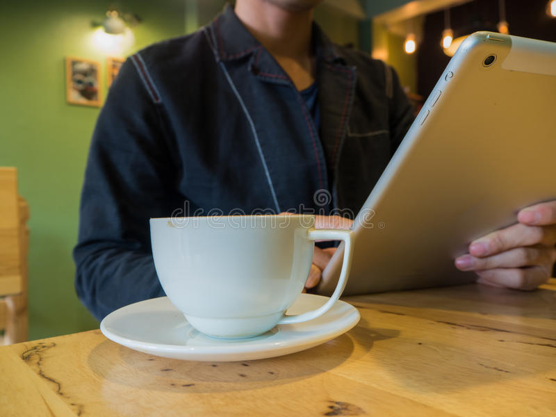 Casual man relaxed using digital tablet with coffee cup royalty free stock photography
