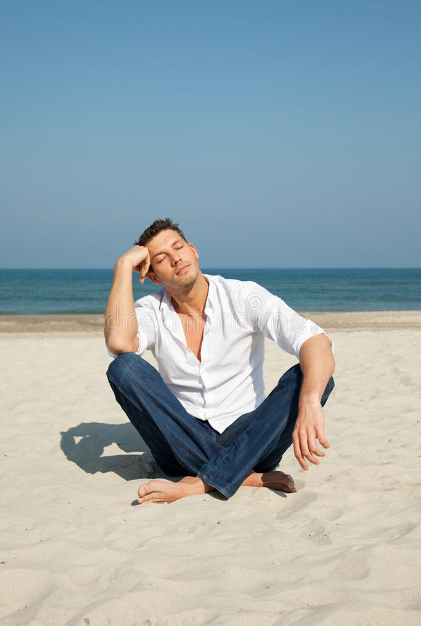 Casual Man Sitting On Beach Royalty Free Stock Photography