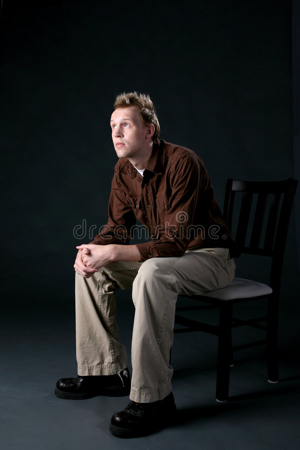 Casual man sitting in a chair and looking up stock photos