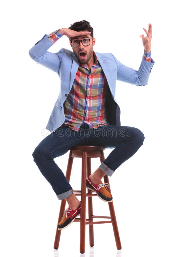 Casual man sitting while making a funny face royalty free stock photography