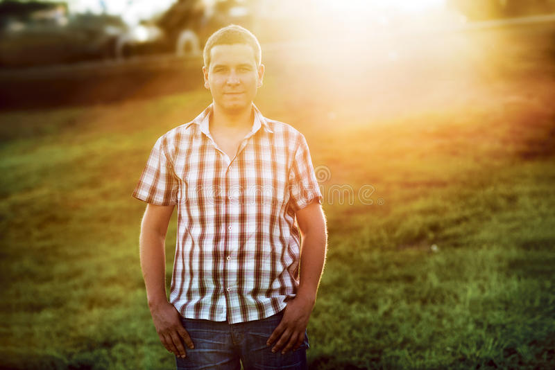 Download Casual Man Standing On The Green Grass In The Park On The Sunset Stock Image - Image: 35079443