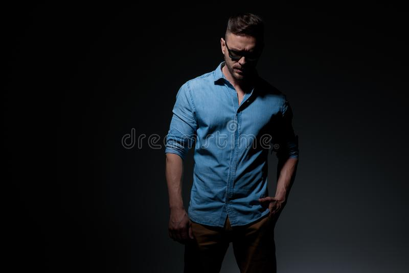 Casual man standing with hand in pocket and looking down stock photos