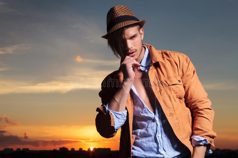 Casual man in the sunset pulling his hair. Casual young man standing outdoor and pulling his hair on his face while looking into the camera with the sunset royalty free stock photos
