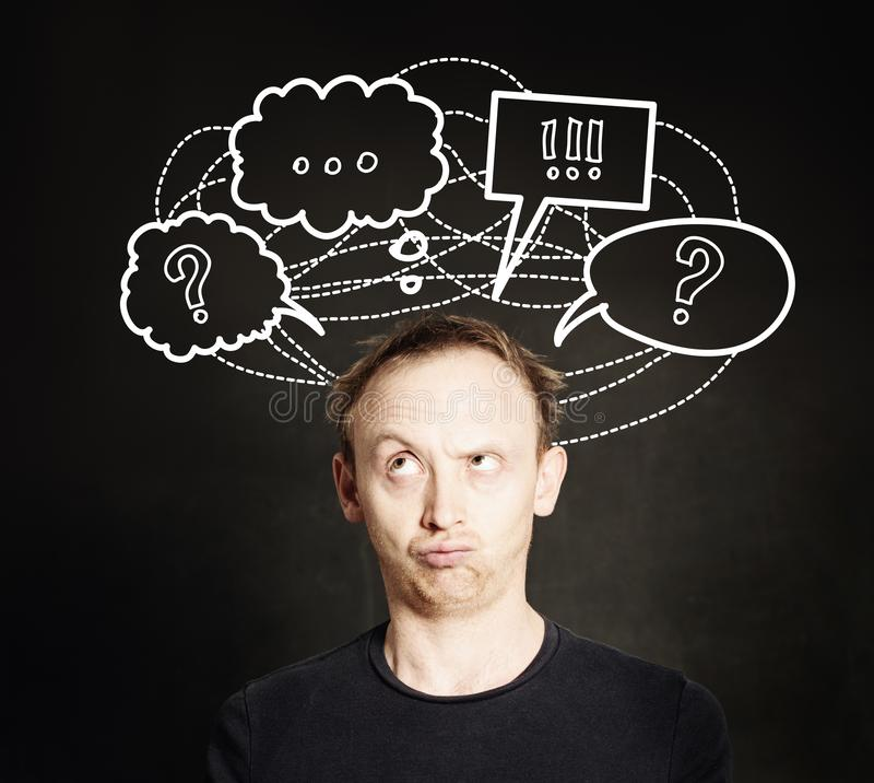 Casual man thinking with question mark and hand drawing sketch bubble on blackboard background. royalty free stock image