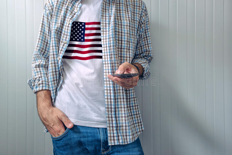 Casual man with USA flag on shirt using mobile phone stock images