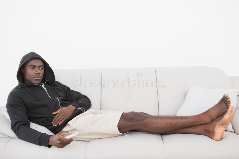 Casual man watching tv on his sofa stock photos