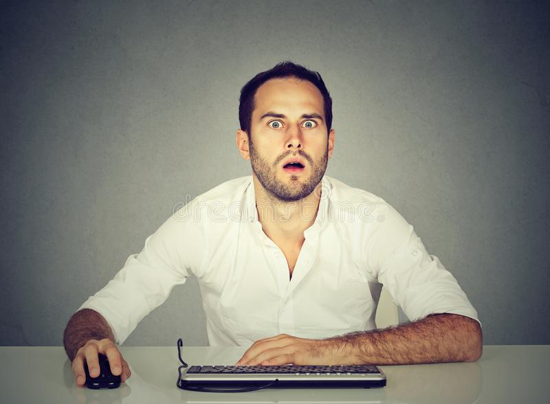 Amazed man using computer at desk royalty free stock photo