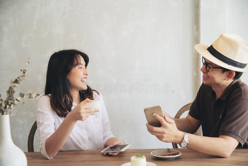 Casual man and woman talking happily while drink coffee and looking mobile phone stock images