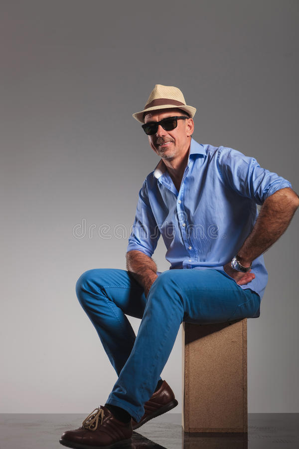 Casual mature man seated hand on waist stock images