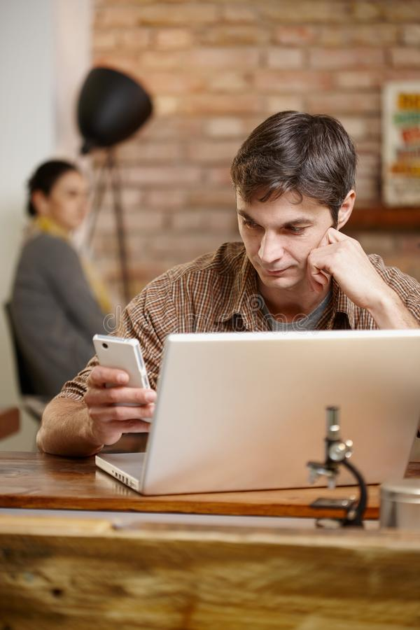 Casual man with mobile and laptop. Casual men using mobile and laptop, sitting at desk stock photography
