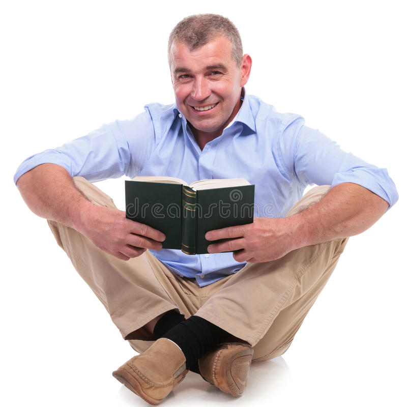 Download Casual Middle Aged Man Sits With Book Stock Photo - Image of feet, folded: 31425812