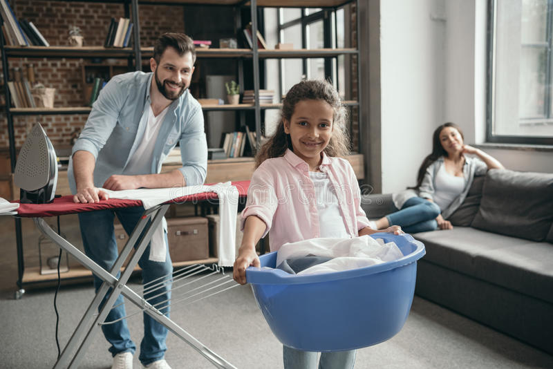 Casual multiethnic family ironing clothes at home. Happy casual multiethnic family ironing clothes at home stock image