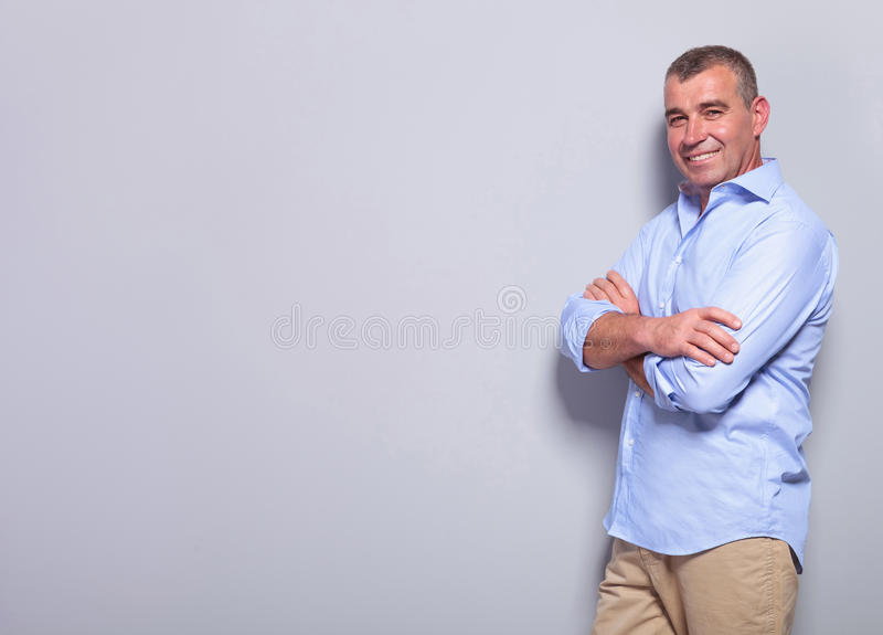 Casual old man with arms crossed on gray stock photo