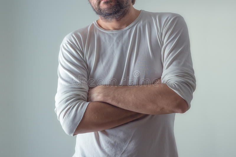 Casual ordinary man in blank white shirt standing, arms crossed. Casual ordinary man in blank white shirt with arms crossed, standing on plain gray background royalty free stock photography