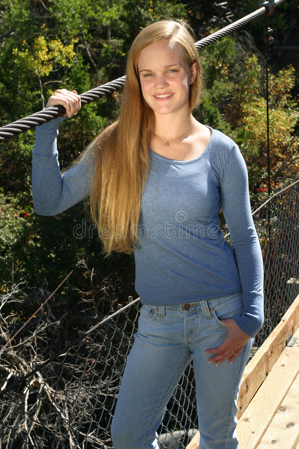 Casual Outdoor Teen Girl. Smiling casual teenage girl standing on a bridge royalty free stock photography