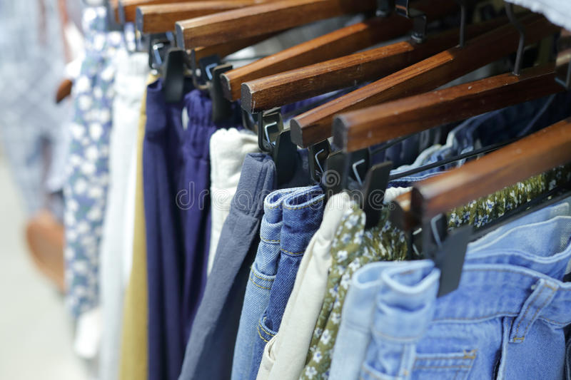 Casual pants on hangers. Jeans on hanger at the show in clothing shop royalty free stock image