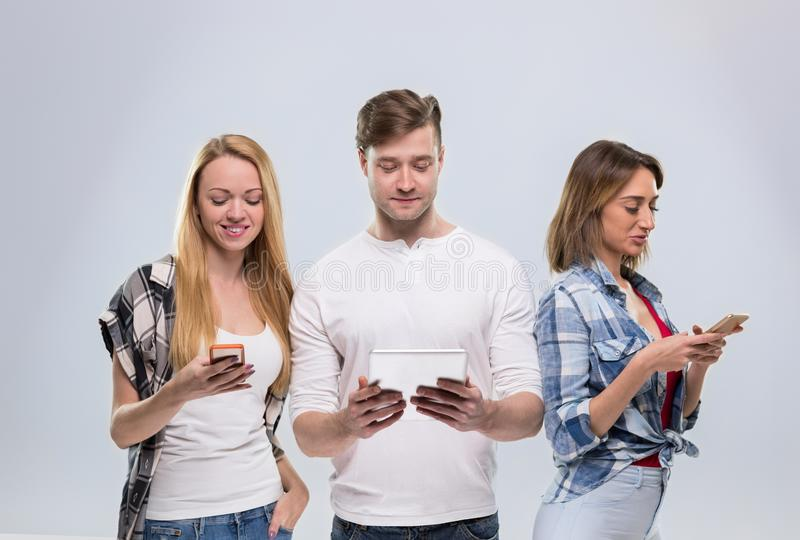 Casual People Group, Young Man Two Woman Happy Smile Using Cell Smart Phone Network Communication. Over Grey Background stock photography