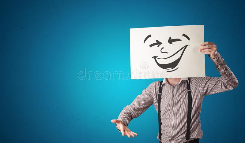 Person holding a paper with cool emoticon face. Casual person holding a paper with cool emoticon in front of his facen stock image
