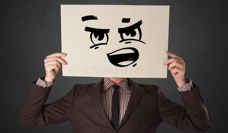 Person holding a paper with funny emoticon in front of her face. Casual person holding a paper with funny emoticon in front of her face stock photo