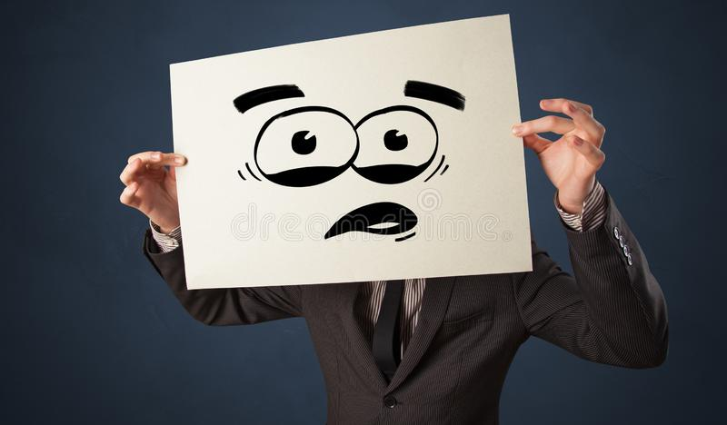 Person holding a paper with funny emoticon in front of her face. Casual person holding a paper with funny emoticon in front of her facen royalty free stock images