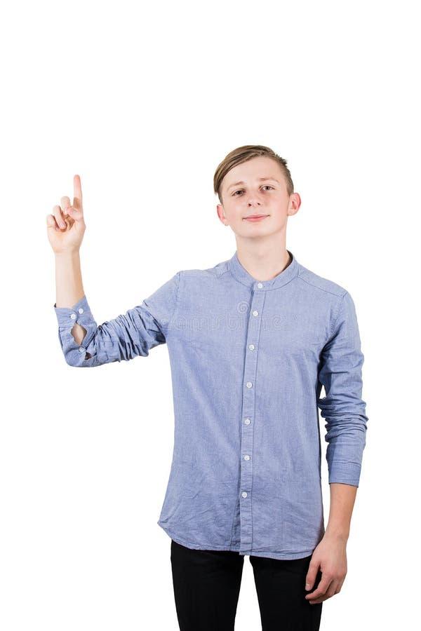 Casual 16-pojken som pekar ut sitt pekfinger isolerat över vit bakgrund royaltyfri bild