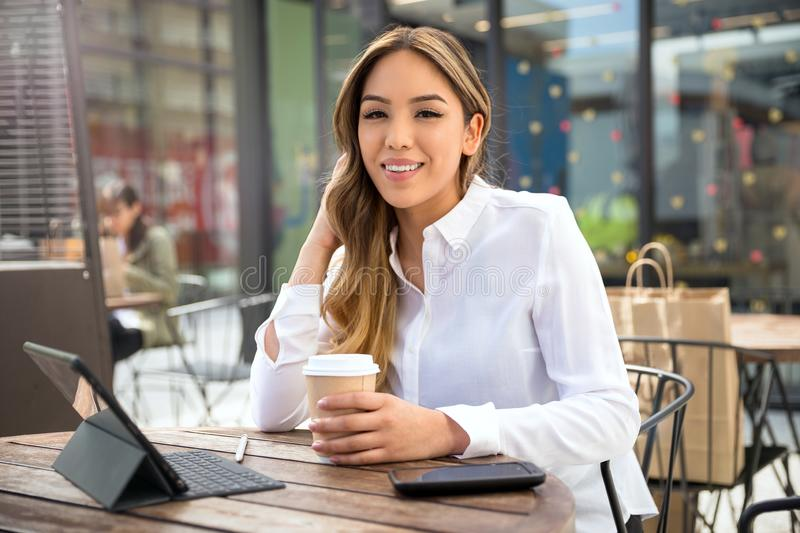 Casual portrait of a mixed race Hispanic and asian young college student, studying on campus coffee shop, online internet and web royalty free stock photography