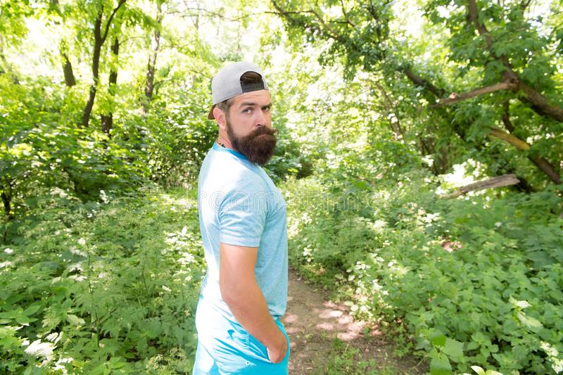 Casual rules. Stylish hipster in casual and comfy outfit travelling on natural landscape. Bearded man wearing casual. Summer style on summer vacation. Casual stock photography